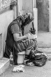 Eine alte arme traurige Frau, die auf einem Bürgersteig nahe dem Bukarest-Stadtzentrum bittet Stockbild