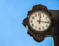 Eine alte Außenuhr mit blauem Himmel Lizenzfreie Stockfotografie