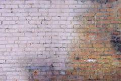 Eine alte Backsteinmauer hergestellt von den roten Backsteinen Der Teil der Wand wird mit einem blassen - rosa Farbe gemalt Leere Stockfotografie