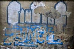 Eine alte Betonmauer mit dem knochenlosen Gips, verdorben durch farbige Graffitizeichnung Lizenzfreie Stockfotos