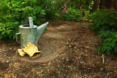 Eine alte Bewässerungsdose und -handschuhe sitzen lizenzfreies stockfoto
