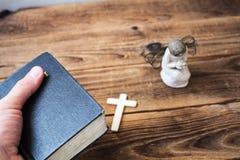 Eine alte Bibel des Engels in der Hand und Kreuz Lizenzfreie Stockbilder