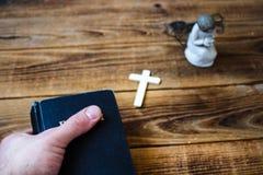 Eine alte Bibel des Engels in der Hand und Kreuz Stockbild