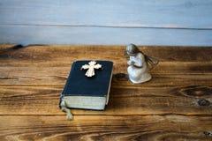 Eine alte Bibel und ein Kreuz des Engels Lizenzfreies Stockfoto
