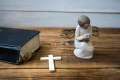 Eine alte Bibel und ein Kreuz des Engels Lizenzfreie Stockfotografie