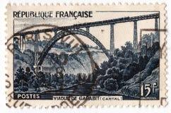 Eine alte blaue französische Briefmarke mit einem Bild der Eisenbahnbrücke Garabit-Viadukts Lizenzfreie Stockfotos