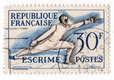 Eine alte blaue französische Briefmarke mit einem Bild eines Mannes in einer Klinge, die Kostüm einzäunt Stockbilder