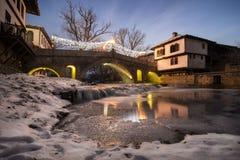 Eine alte Brücke über einem gefrorenen Fluss Stockbilder