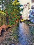 Eine alte Brücke über einem Strom bedeckt in einem glänzenden roten flowin stockfoto