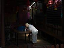 Eine alte Dame isst das Abendessen in einem Lichtstrahl Lizenzfreie Stockfotos