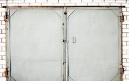 Eine alte Eisentür geschlossen mit Backsteinmauer Stockfotos