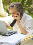 Eine alte Frau arbeitet an einem tragbaren Computer und spricht über m Lizenzfreie Stockfotos