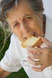 Eine alte Frau beißt einen getrockneten Toast Lizenzfreies Stockfoto
