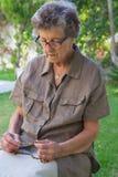 Eine alte Frau betet im Garten Stockfotografie