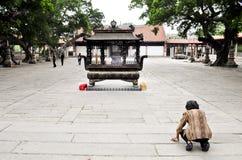 Eine alte Frau betet zu einem kleinen Schrein Stockfotos
