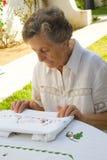 Eine alte Frau betrachtet die Ergebnisse ihrer handgemachten Arbeit Stockfoto