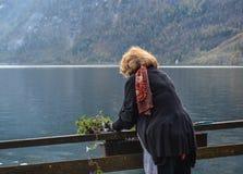 Eine alte Frau, die den See betrachtet stockfoto