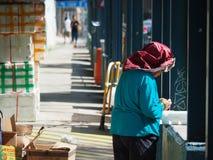 Eine alte Frau, die in den Straßen von Kowloon arbeitet und einen Stoff auf ihrem Kopf trägt, um sich zu schützen stockfotografie