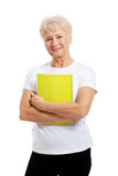 Eine alte Frau, die ein Arbeitsbuch hält. lizenzfreies stockbild