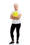Eine alte Frau, die ein Arbeitsbuch hält. lizenzfreie stockbilder