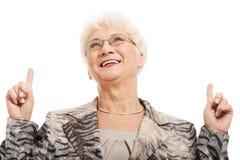Eine alte Frau, die oben mit den Fingern zeigt. Lizenzfreies Stockfoto