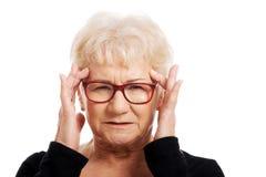 Eine alte Frau ist Augengläser hat Kopfschmerzen. stockfotografie