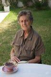 Eine alte Frau liest ein Buch im Garten Lizenzfreie Stockfotos