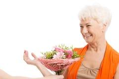 Eine alte Frau mit Blumenstrauß von Blumen. Stockfoto