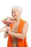 Eine alte Frau mit Blumenstrauß von Blumen. Stockfotografie