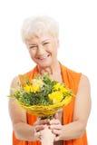 Eine alte Frau mit Blumenstrauß von Blumen. Stockfotos