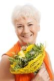 Eine alte Frau mit Blumenstrauß von Blumen. Lizenzfreie Stockbilder