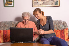 Eine alte Frau mit einem Laptop Stockbild