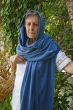 Eine alte Frau mit gesponnenem Korb Stockfotos