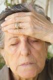 Eine alte Frau mit starken Kopfschmerzen Stockfotografie
