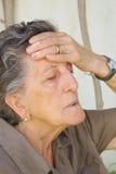 Eine alte Frau mit starken Kopfschmerzen Stockbild