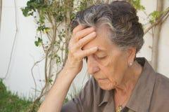 Eine alte Frau mit starken Kopfschmerzen Lizenzfreie Stockfotografie