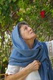 Eine alte Frau mit umfaßtem Kopf betrachtet den Himmel Stockfotografie