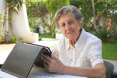Eine alte Frau passt eine Tablette auf Stockfoto