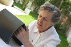 Eine alte Frau passt eine Tablette auf Stockfotos