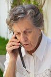 Eine alte Frau spricht am Telefon Stockfotografie