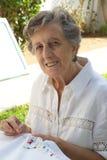 Eine alte Frau stickt auf der weißen Decke Lizenzfreies Stockbild