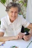 Eine alte Frau wählt herauf eine Telefonnummer auf ihrem Smartphone Lizenzfreie Stockfotografie