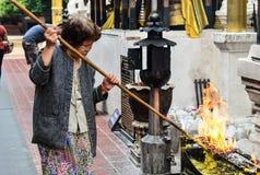 Eine alte Frau, welche die Kerzenrisse auswählt Lizenzfreie Stockfotos