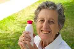 Eine alte Frau zeigt das Produkt, das sie mit zufrieden ist Lizenzfreies Stockfoto