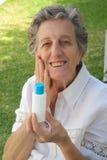 Eine alte Frau zeigt das Produkt, das sie mit zufrieden ist Stockbild