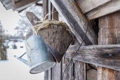 Eine alte Gartenwasserscheide und eine alte Hacke hingen an der Wand im Winter Lizenzfreies Stockfoto