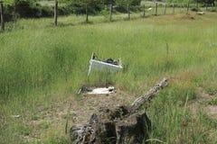 Eine alte, gebrochene Waschmaschine, unvorsichtig weggeworfen auf Wiese lizenzfreie stockbilder