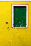 Eine alte gelbe Wand mit einem grünen Fenster Stockfotos