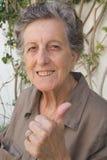 Eine alte glückliche Frau zeigt, dass sie erfüllt und mit ihrem Leben glücklich ist Lizenzfreie Stockbilder