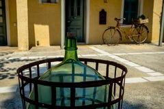 Eine alte Glaswein-Flasche im Hof mit einer alten Fahrradfelge stockfotos